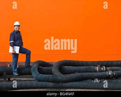 Un travailleur de l'Administration portuaire de l'inspection d'un navire de marchandises tuyaux de carburant. Banque D'Images