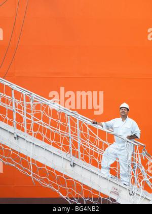 Une autorité portuaire worker un escalier jusqu'à un quai de bateau de marchandises. Banque D'Images