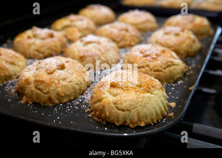 Fait maison fraîchement sorti de petits pâtés sur plaques de cuisson frais hors du four dans une cuisine maison Banque D'Images