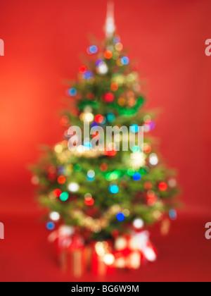 Des problèmes de mise au point de l'arbre de Noël décoré isolé sur fond rouge