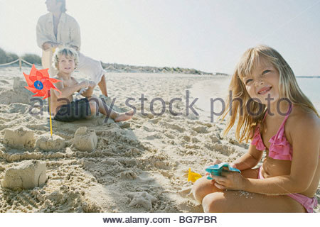 Family playing in sand on beach Banque D'Images