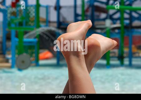 Les pieds nus du jeune femme de détente sur chaise longue près d'une piscine dans un parc de l'eau Banque D'Images