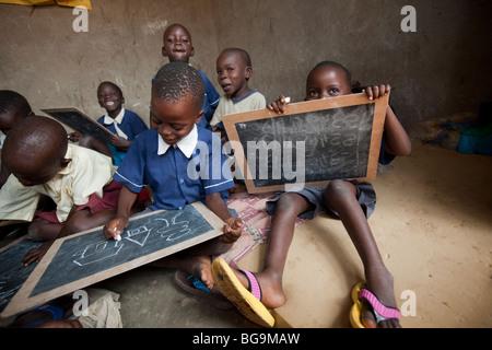 Les jeunes enfants de dessiner sur les tableaux dans un orphelinat à Amuria, Ouganda, Afrique de l'Est. Banque D'Images
