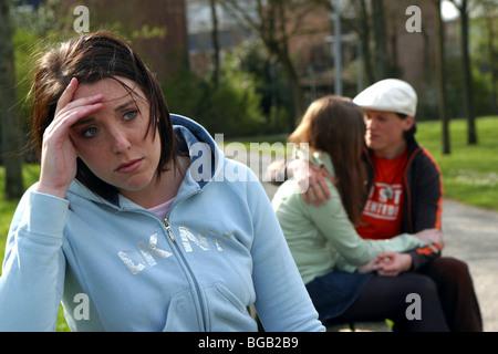 Envieux ou ennuyer ami et les amis de flirter à l'extérieur sur banc de parc. Banque D'Images