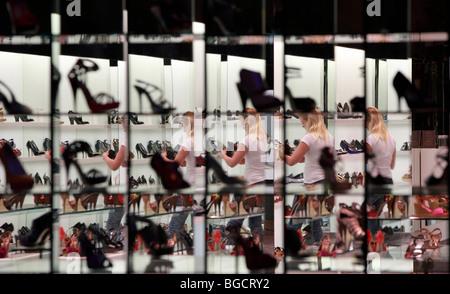 Une femme à la recherche de chaussures dans un magasin de chaussures, Dubaï, Émirats Arabes Unis Banque D'Images