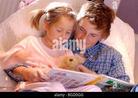 Frère est en train de lire une histoire à sa sœur Banque D'Images