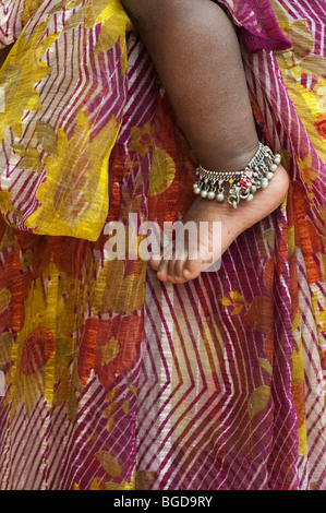 Les bébés indiens pied nu portant un bracelet de cheville contre les mères à motifs à rayures sari. L'Andhra Pradesh, Banque D'Images