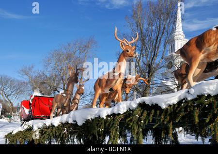 Le traîneau du Père Noël et des rennes à Noël avec la neige et le clocher de l'église et ciel bleu