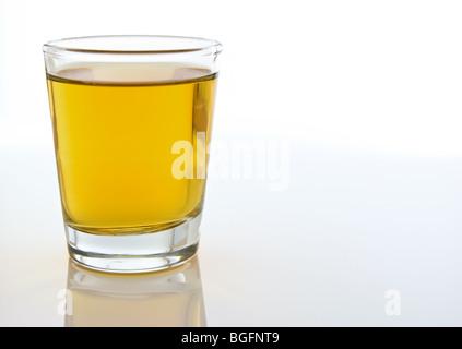 Un gros plan d'un shot compsition verre rempli d'alcool de couleur orange sur un fond blanc.
