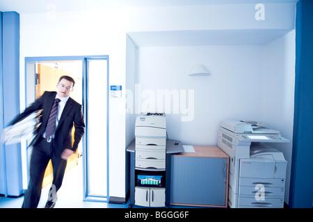 Homme d'affaires surmené entre dans une chambre, blurred motion, front view Banque D'Images