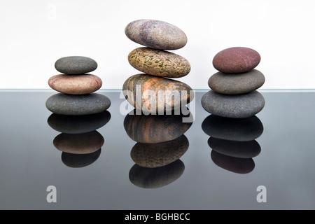La vie toujours tourné de trois piles de cailloux plage contre fond noir et blanc avec la réflexion Banque D'Images