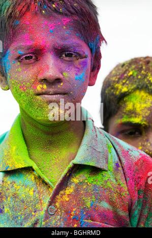 Les jeunes garçons indiens couverts en pigment poudre de couleur sur un fond blanc. L'Inde Banque D'Images