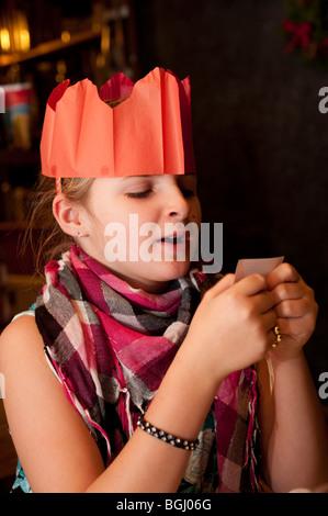 Enfant portant un chapeau de fête en papier la lecture d'une blague d'un cracker de Noël