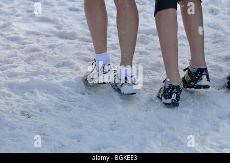 Les jeunes filles sur la ligne de départ de la course cross-country race debout dans la neige, UK Banque D'Images