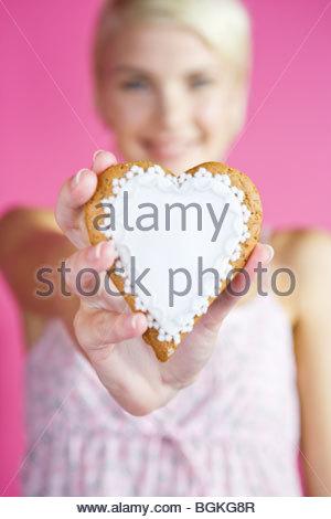 Une jeune femme tenant un biscuit en forme de coeur Banque D'Images
