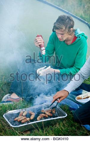 Deux jeunes hommes cooking sausages on a barbecue Banque D'Images