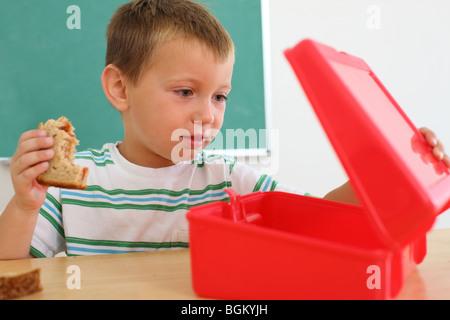 Jeune garçon regarde dans lunch box Banque D'Images