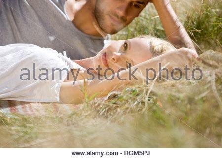 Un jeune couple romantique de détente sur l'herbe Banque D'Images