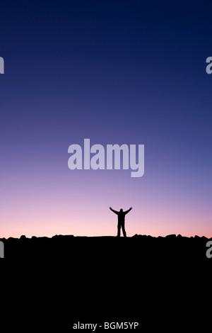 Silhouette d'un homme levant les mains dans le lever du soleil après la conquête d'un sommet Banque D'Images