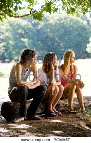 Trois jeunes gens assis sur un journal, dans un parc Banque D'Images