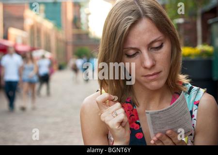 Jeune femme jouant une loterie à gratter, tenant une pièce de monnaie