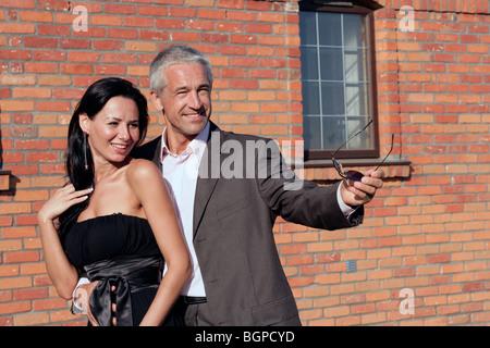 Joli couple heureux debout à côté d'un mur de briques Banque D'Images