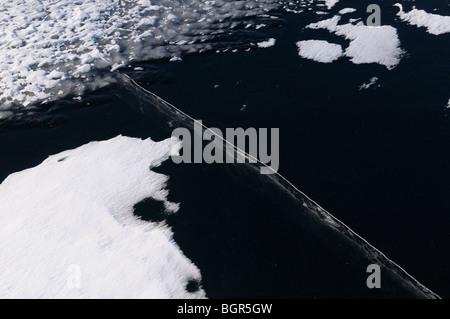 Glace noire sur un lac avec une grande fissure profonde et de surface ondulée et des amoncellements de neige Banque D'Images
