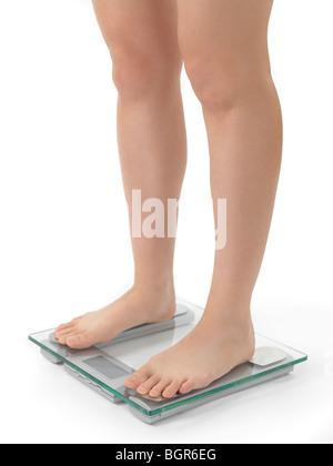 Femme debout sur une échelle de poids. Isolé sur fond blanc. Banque D'Images