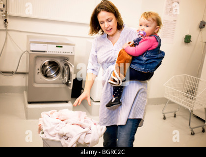 Femme faire la lessive avec sa petite fille, la Suède. Banque D'Images