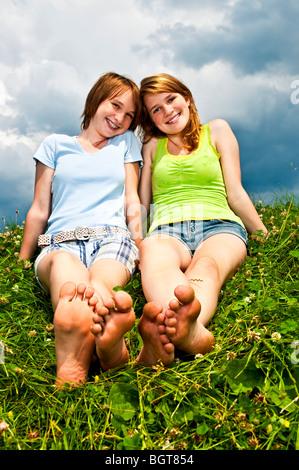 Deux jeunes teenage girl friends sitting pieds nus sur summer meadow Banque D'Images