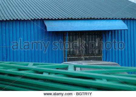 Fenêtre sur un builoding bleu fabriqué à partir de tôles ondulées galvanisées Banque D'Images