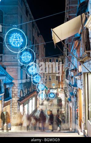 Les touristes marcher la nuit sur le pont du Rialto à la recherche à l'boutiques sous les décorations de Noël avec Banque D'Images