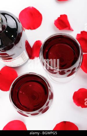 Une paire de verres de vin remplis de vin rouge entourée de pétales de rose rouge sur un fond blanc et une bouteille Banque D'Images