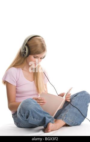 Teenage girl sitting avec jambes croisées d'écouter de la musique et de la lecture livre Banque D'Images