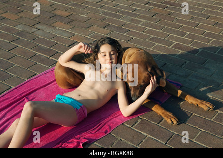 Girl lying on dog Banque D'Images