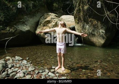 Girl standing on rock in stream Banque D'Images