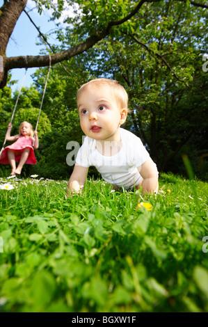 Bébé dans le jardin, la fille sur la balançoire Banque D'Images