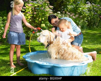 Mère, fille et fils lave le chien Banque D'Images