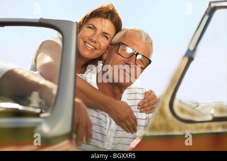 Senior couple embracing in sports car Banque D'Images