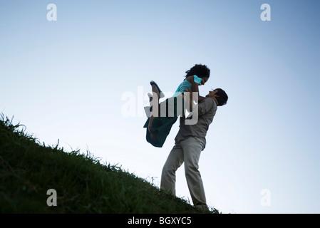 Jeune couple, femme de sauter dans les bras de l'homme Banque D'Images