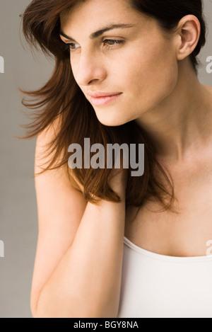 Jeune femme avec la main dans les cheveux, portrait Banque D'Images