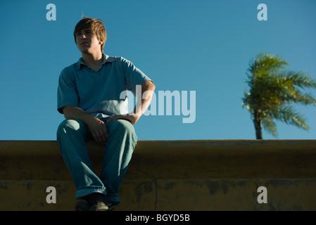 Jeune homme assis sur le rebord, à l'écart Banque D'Images