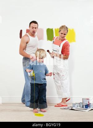 Bébé garçon pouring peindre sur le tapis Banque D'Images