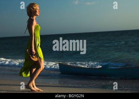 Femme en robe d'walking on beach, à la recherche en mer Banque D'Images