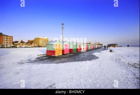 Neige sur Brighton et Hove Beach avec les cabines colorées dans l'avant-plan Banque D'Images