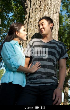 Jeune couple se placer à côté de l'arbre dans le parc Assiniboine, Winnipeg, Manitoba, Canada Banque D'Images