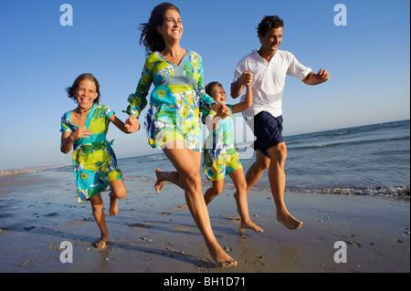 Famille d'exécution sur la plage ensemble Banque D'Images