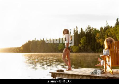 Femme debout en maillot, deuxième femme assise dans une chaise sur dock, Clear Lake, Manitoba, Canada