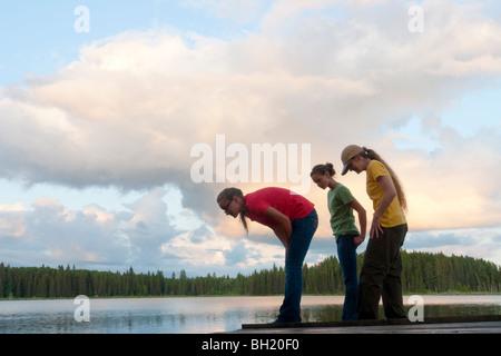 Femme et deux filles à la station d'arrêt vers le bas dans l'eau, lac Katherine, Manitoba, Canada Banque D'Images