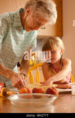 Petite fille de cinq ans aider grand-mère Préparer la pâte; Redvers, Saskatchewan, Canada Banque D'Images
